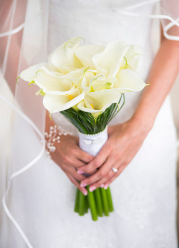 "<img alt=""bride holding a bouquet of white calla lilies"">"
