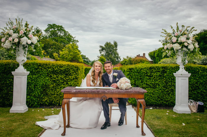 Bride and groom sitting at a table in walled garden at Four Seasons Hampshire between urns of decorated with Moutan flowers